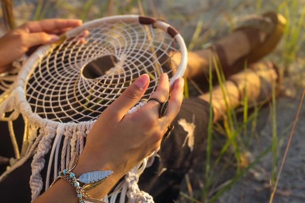 Una niña se sienta en la hierba y sostiene un atrapasueños.