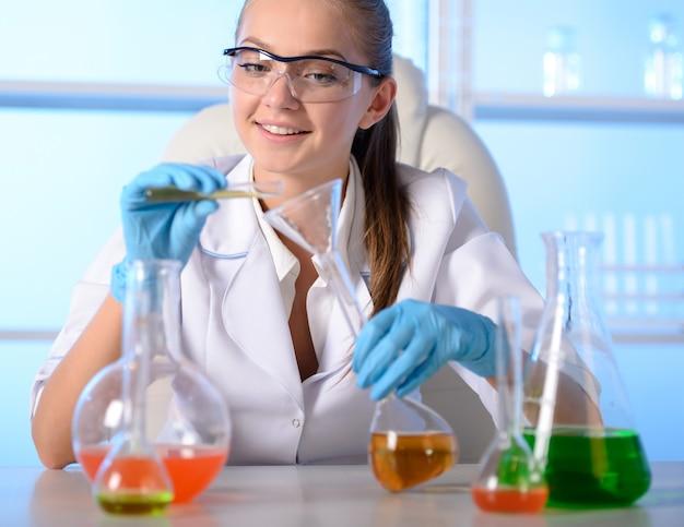 La niña se sienta en el laboratorio y realiza experimentos.