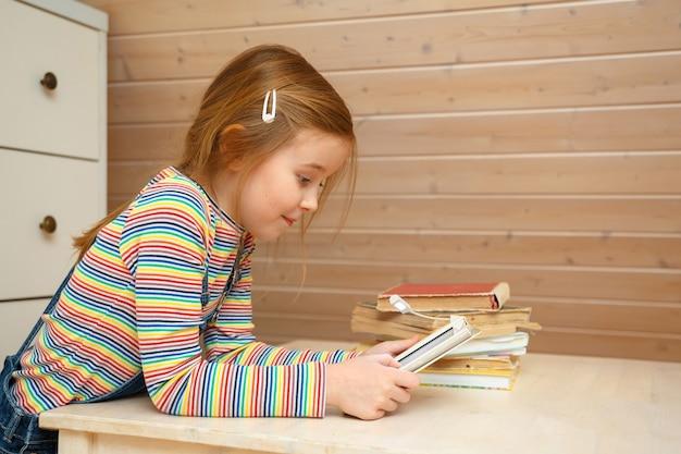 La niña se sienta en una mesa y lee un libro electrónico.