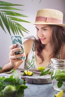 Una niña se sienta en una mesa con un sombrero y se toma una selfie