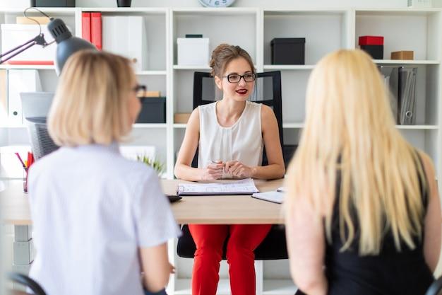 Una niña se sienta en una mesa de su oficina y habla con dos compañeros.