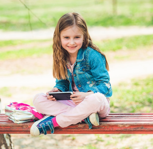 Niña se sienta con su teléfono en el parque