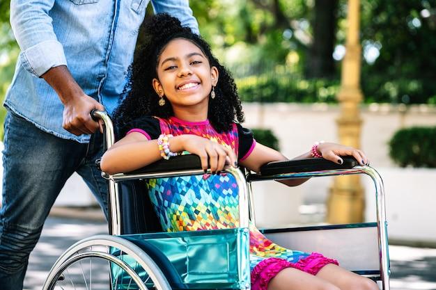 Una niña en silla de ruedas disfrutando y divirtiéndose al aire libre mientras su padre la empuja por la calle.