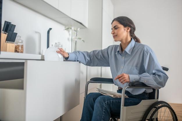 Una niña en silla de ruedas haciendo tareas domésticas y mirando involucrada