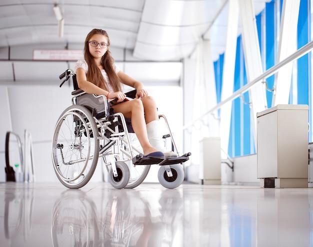 Una niña en silla de ruedas está leyendo un libro. paciente en silla de ruedas en el pasillo del hospital.