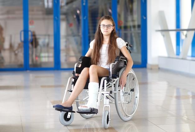 Una niña en silla de ruedas está de pie en el pasillo del hospital.