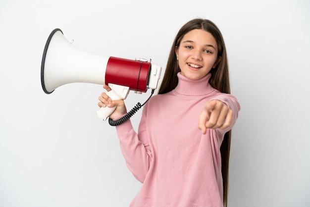 Niña sobre fondo blanco aislado sosteniendo un megáfono y sonriendo mientras apunta hacia el frente