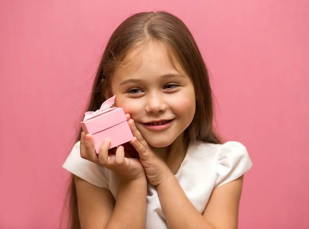 Niña sobre un fondo rosa con caja de regalo