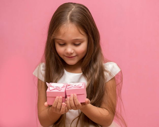Niña sobre un fondo rosa con cajas de regalo