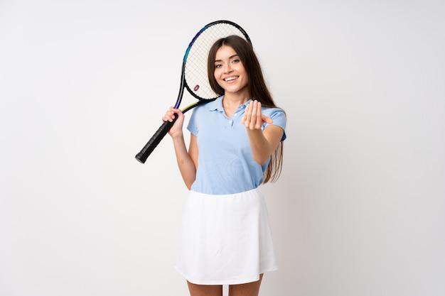 Niña sobre pared blanca aislada jugando al tenis y haciendo gesto que viene