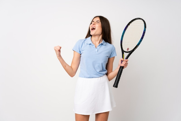 Niña sobre pared blanca aislada jugando tenis y celebrando una victoria