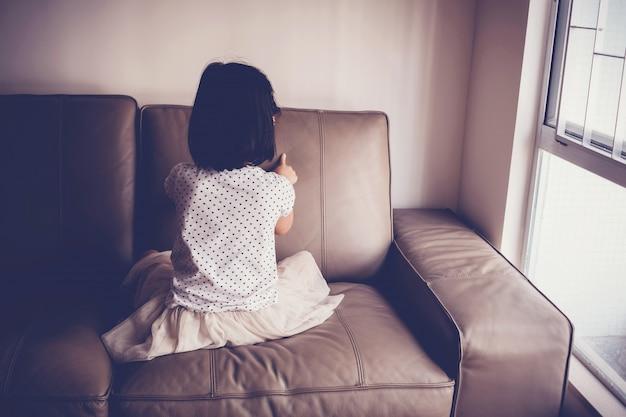 Niña sola que juega sola en el sofá en casa, concepto de austism y salud mental infantil