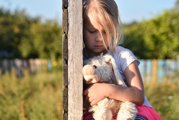 Niña solitaria en la calle está triste y tiene una liebre de juguete con las manos