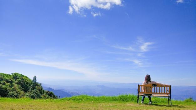 Niña solitaria que se sienta en el banco en jardín en el paisaje de la montaña y del cielo.
