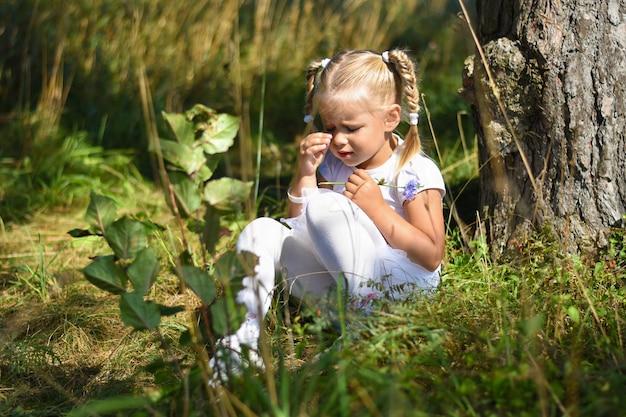 Niña solitaria y triste con un vestido blanco y una flor en la mano se perdió en el bosque, sentada cerca de un árbol y llorando durante el día.