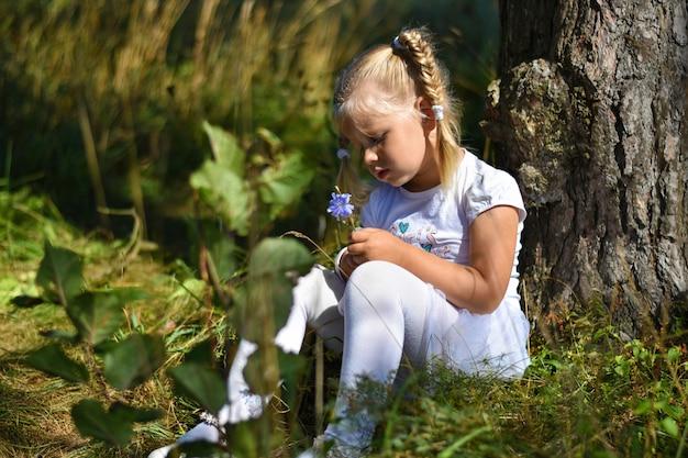 La niña solitaria con un vestido blanco y una flor en la mano se sienta cerca de un árbol en la tarde