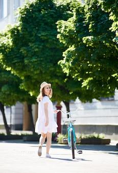 Niña solitaria viene con una bicicleta retro en la calle soleada de la ciudad con espacios verdes