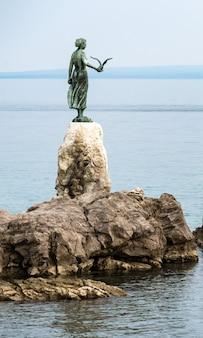 Niña soltera sosteniendo una gaviota y mirando al mar, estatua en las rocas, opatija