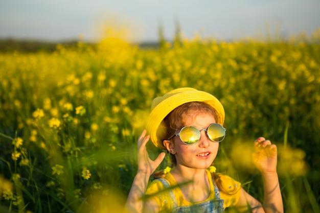 Una niña con un sombrero amarillo y gafas redondas mira al sol en un campo floreciente de verano. horario de verano, puesta de sol, festivos, protectores solares, alergias, repelente de mosquitos.