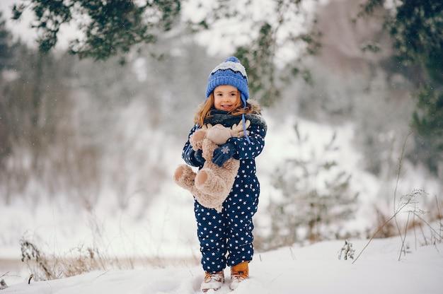 Niña en un sombrero azul jugando en un bosque de invierno