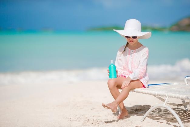 Niña con sombrero con botella de crema solar sentado en la playa tropical