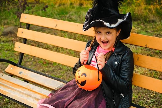Niña con sombrero de bruja en el parque otoño.
