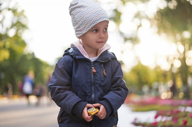 Niña con sombrero cálido chaqueta de otoño camina por el parque de otoño con coche de juguete
