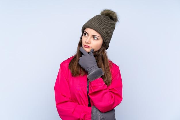 Niña con sombrero de invierno aislado en azul con dudas y con expresión de la cara confusa