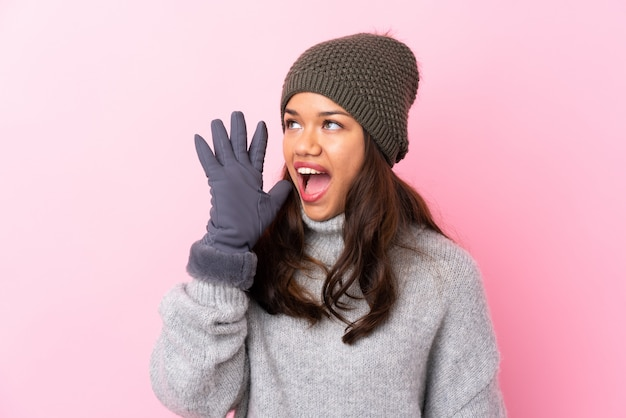 Niña con sombrero de invierno sobre pared rosa gritando con la boca abierta