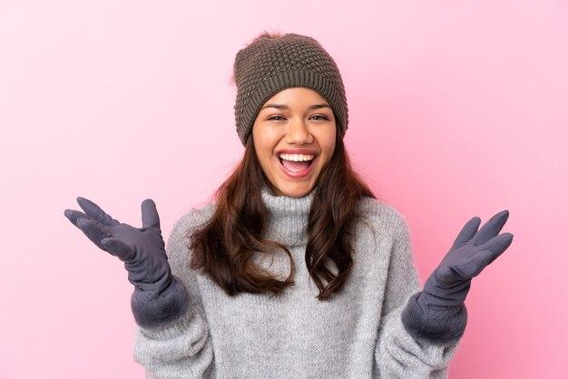 Niña con sombrero de invierno sobre pared rosa infeliz y frustrada con algo