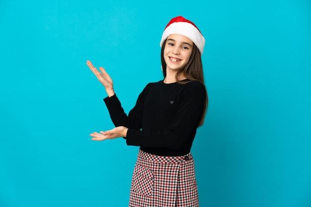 Niña con sombrero de navidad aislado sobre fondo azul extendiendo las manos hacia el lado para invitar a venir