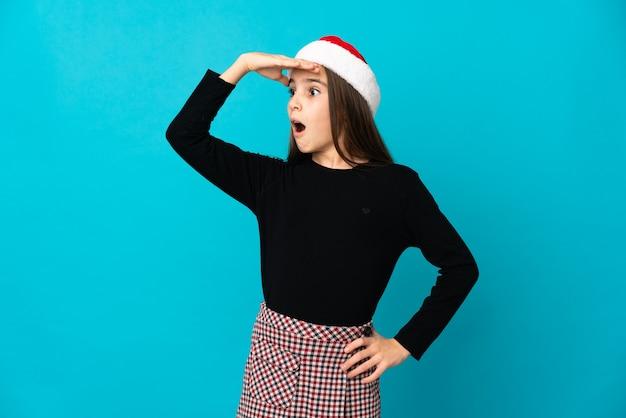 Niña con sombrero de navidad aislado sobre fondo azul haciendo gesto de sorpresa mientras mira hacia el lado