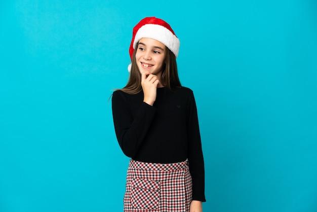 Niña con sombrero de navidad aislado sobre fondo azul mirando hacia el lado y sonriendo