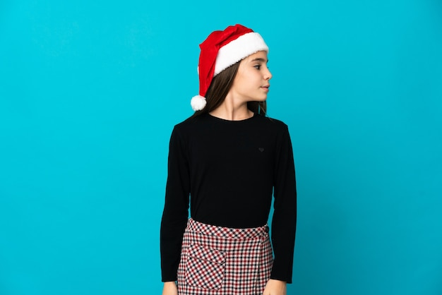 Niña con sombrero de navidad aislado sobre fondo azul mirando hacia el lado