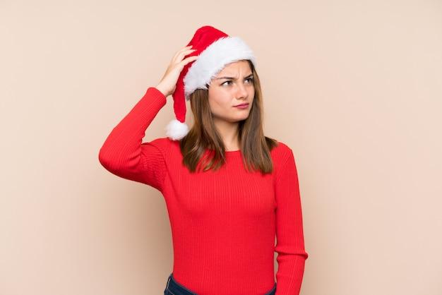 Niña con sombrero de navidad sobre fondo aislado con dudas y con expresión de la cara confusa