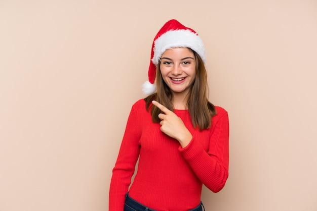 Niña con sombrero de navidad sobre pared aislada apuntando con el dedo al lado