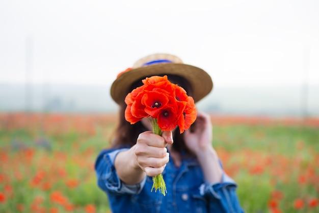 Una niña con un sombrero de paja sostiene un ramo de hermosas amapolas rojas en su mano.