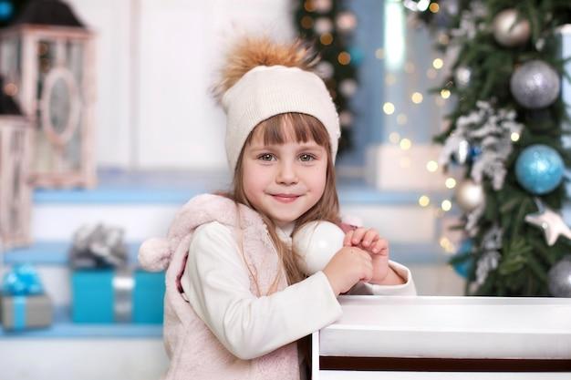Niña con sombrero de pie cerca de buzón en el patio de invierno. la niña envió una carta a santa claus con una lista de regalos de navidad. el niño envía un mensaje al polo norte.