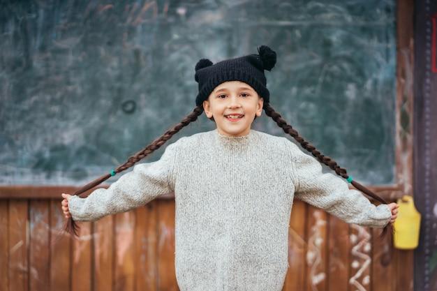 Niña con un sombrero posando delante de una pizarra
