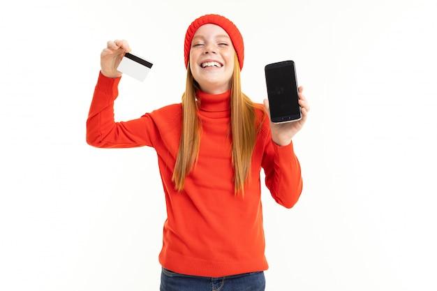 Niña con sombrero rojo se regocija al nuevo teléfono con una tarjeta de crédito en la mano