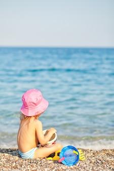 Niña con sombrero rosa jugando con juguetes en la playa.