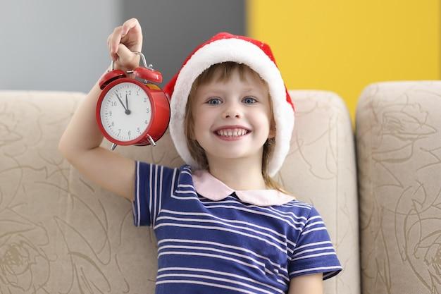 Niña con sombrero de santa claus se sienta en el sofá sonriendo y sosteniendo un despertador