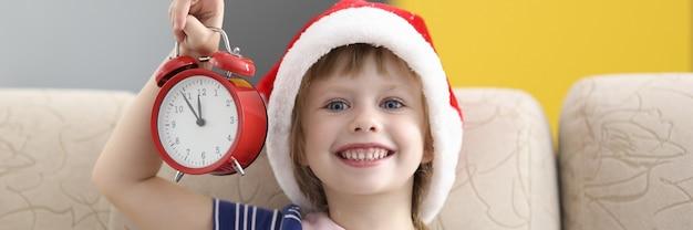 Niña con sombrero de santa claus se sienta en el sofá sonriendo y sosteniendo un despertador.