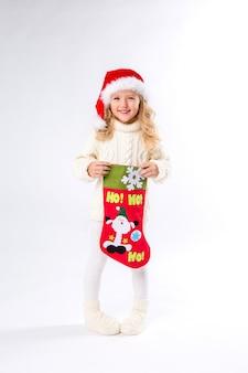 Niña con un sombrero de santa está sosteniendo un calcetín de navidad