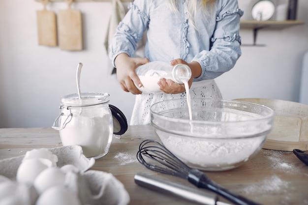 Niña en un sombrero de shef blanco cocinar la masa para galletas