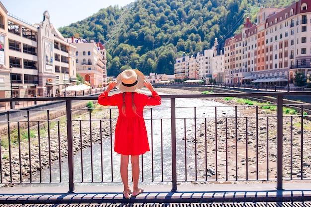 Niña en el sombrero en el terraplén de un río de montaña en una ciudad europea,