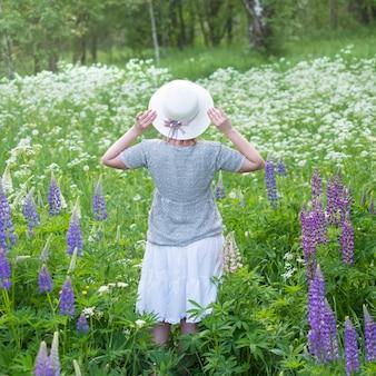 Una niña con un sombrero vestido de estilo retro está de pie con la espalda contra un fondo de un campo de altramuces silvestres de color púrpura y flores blancas.