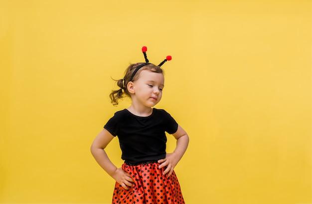 Niña soñadora en un traje de mariquita mira hacia otro lado en un amarillo aislado