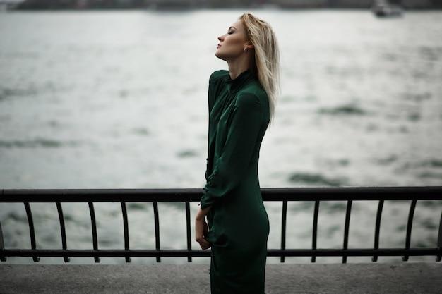 Niña soñadora en vestido verde se encuentra en el terraplén