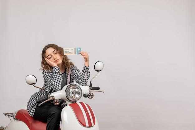 Niña soñolienta en ciclomotor sosteniendo el boleto en gris